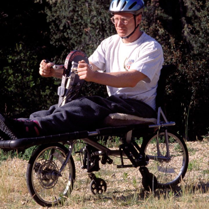 a rider's legs are extended forward while rotating cycle with hands